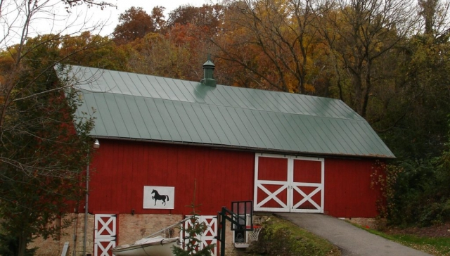Hip barn standing seam metal roofing green
